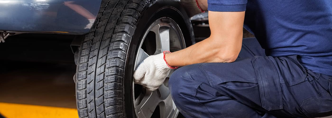 Mechanic Fixing Car Tire At Repair Shop