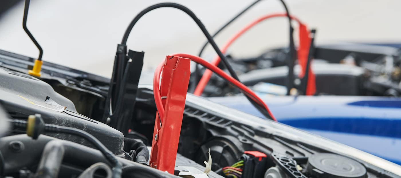 Jumper cables being used to jump start a car