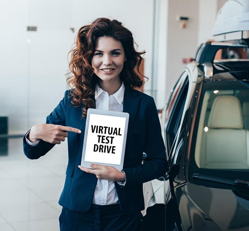 A woman at a BMW dealership holding a virtual test drive sign.