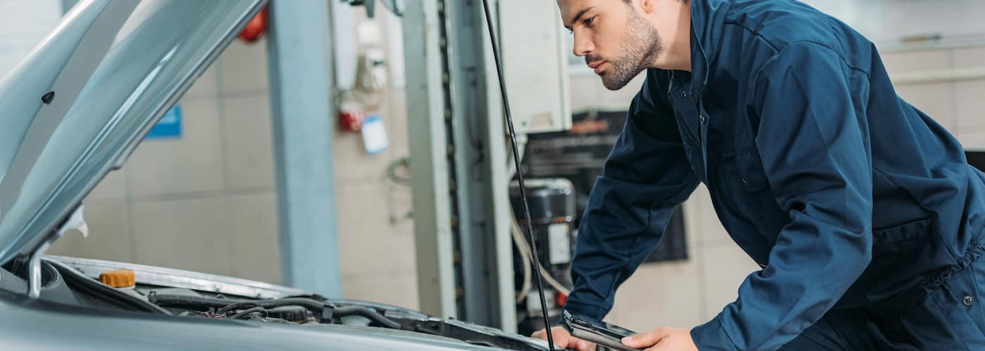 An auto mechanic preparing to check a car's transmission fluid.