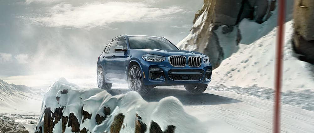 A 2020 BMW X3 driving on a snowy mountain road