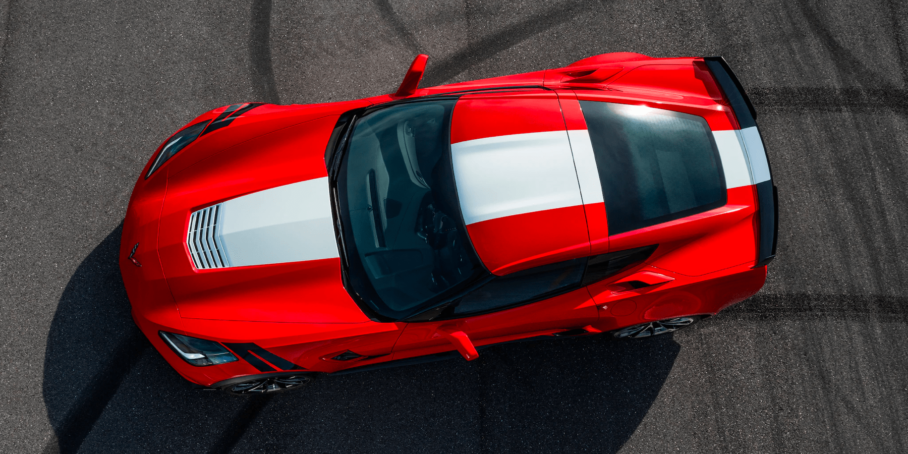looking down at a parked red and white Corvette Z06