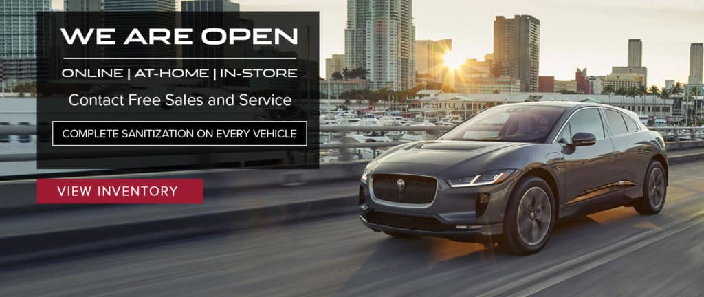 Alt Text: WE ARE OPEN. ONLINE. IN-STORE. CAR SHOPPING. CONTACT-FREE DELIVERY. TEST DRIVES. VEHICLE TRADE-INS. SERVICE PICK-UP AND DROP-OFF. COMPLETE SANITATION ON EVERY VEHICLE. VIEW OUR SPECIALS. RED JAGUAR I-PACE DRIVING UP ROAD IN CITY.