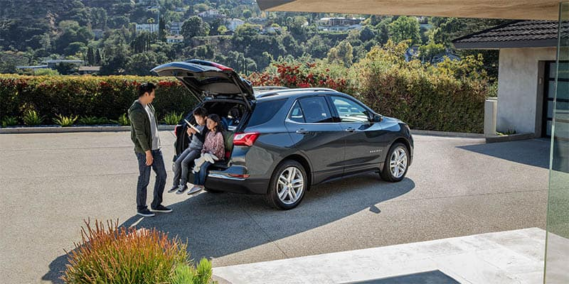 Family sitting in cargo area of Chevy Equinox