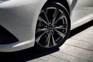 The shiny wheel of a white lexus sedan or coupe atop a very smooth looking brick surface and the wheel is slightly tilted to the right