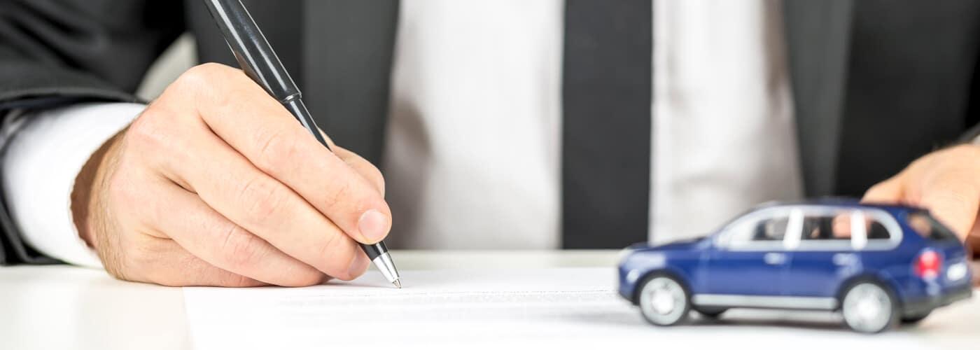 Car finance paperwork with tiny blue car