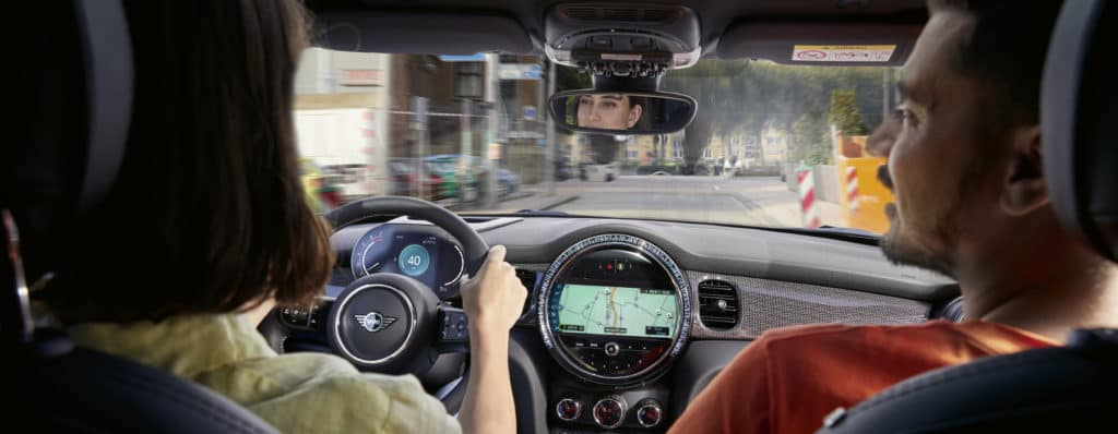 Picture shows a couple sitting in the driver and passenger seats of a 2022 MINI model. The picture is taken from the back seat of the car.