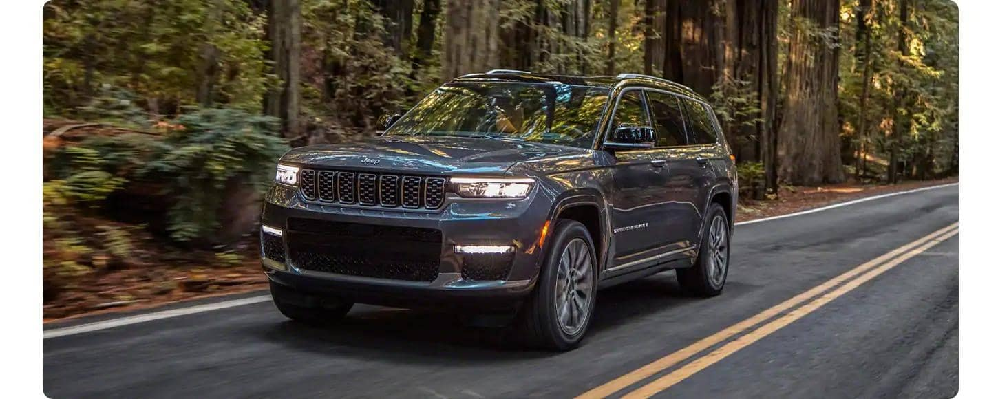 Grand Cherokee L driving through forest three-quarter view