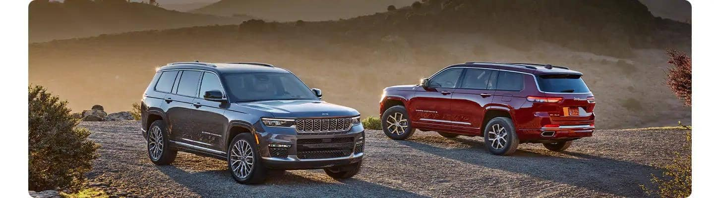 Two New Jeep Grand Cherokee L parked on cliff at sunset