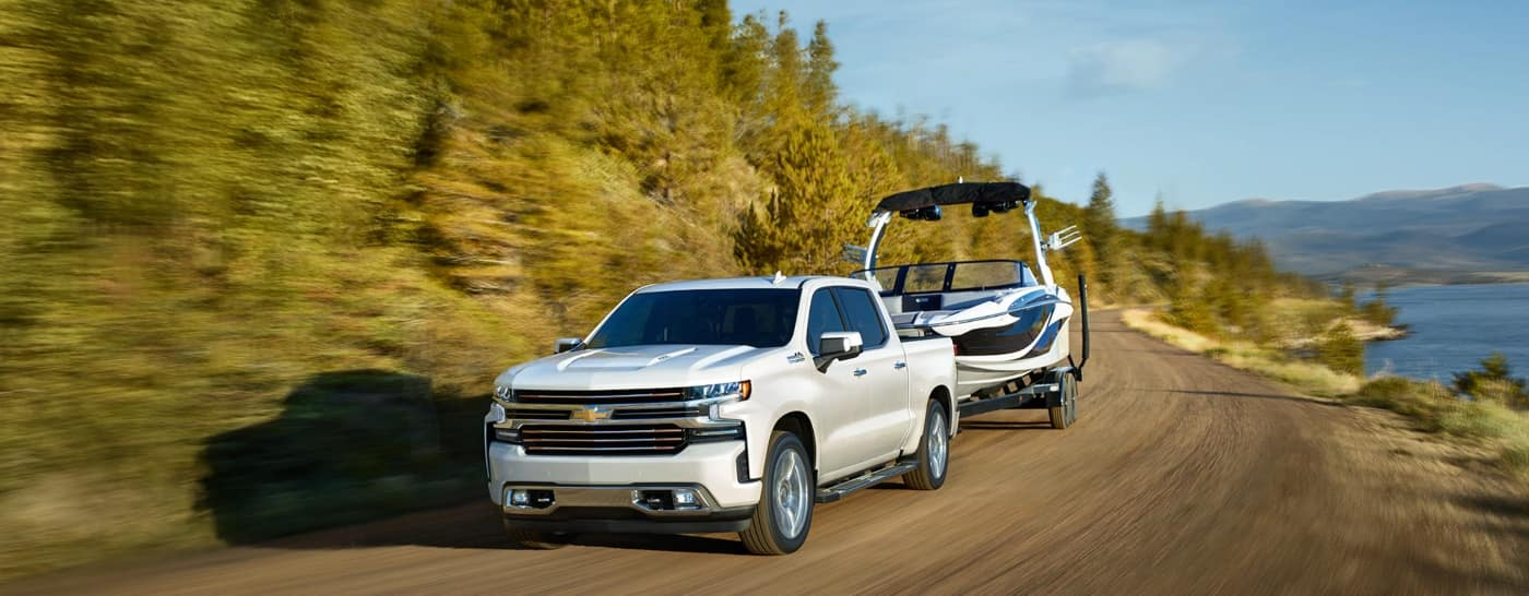 White 2020 Chevy Silverado 1500 towing a boat on the coastline