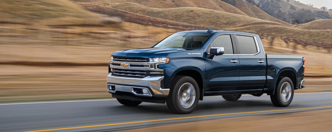 blue 2020 chevy silverado driving through rural area