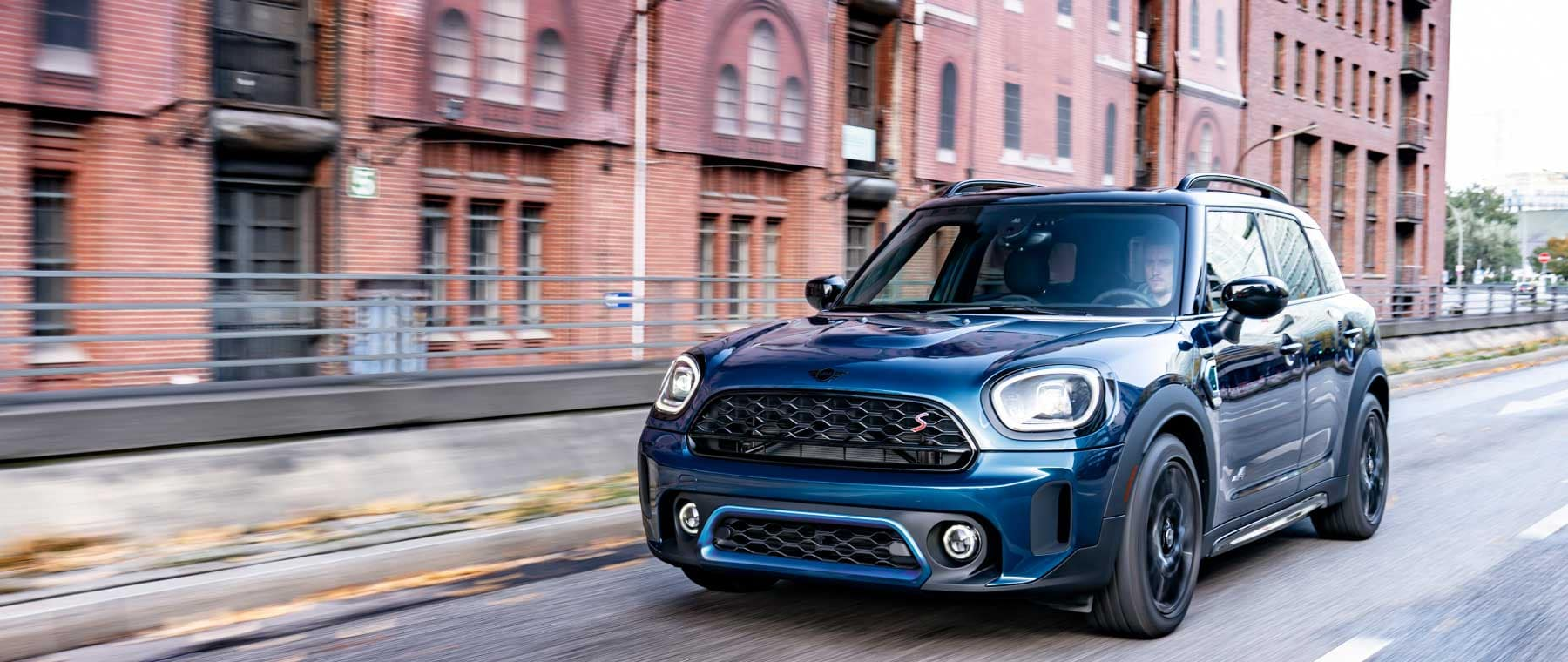 Image shows a man driving a Boardwalk Edition 2022 Countryman down the road in an urban city.