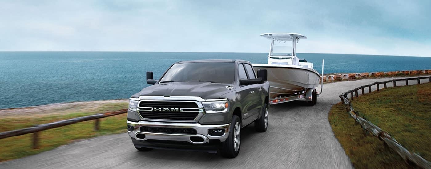 Gray 2020 Ram 1500 towing boat on coastline