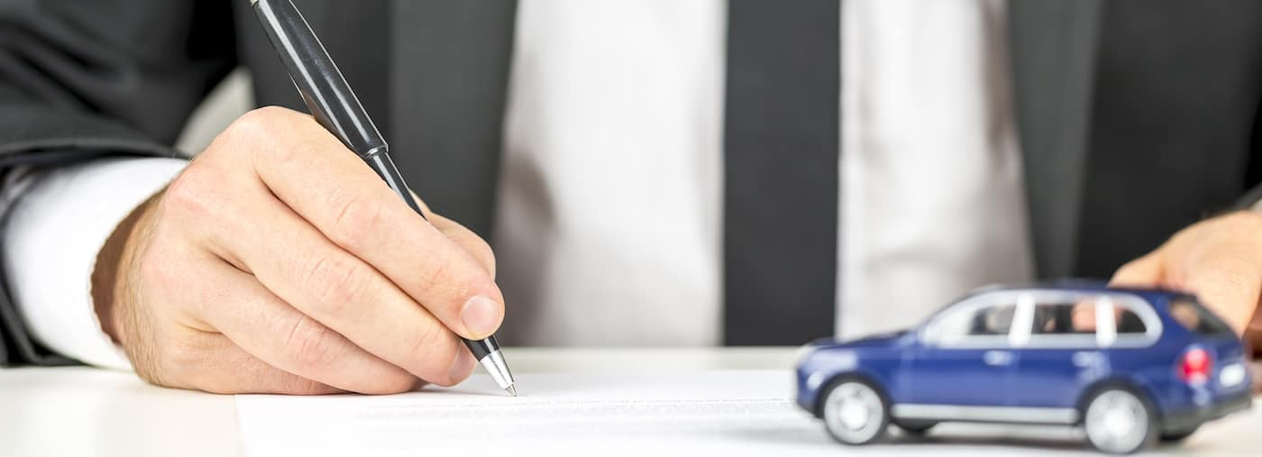 Car finance paperwork with little blue car