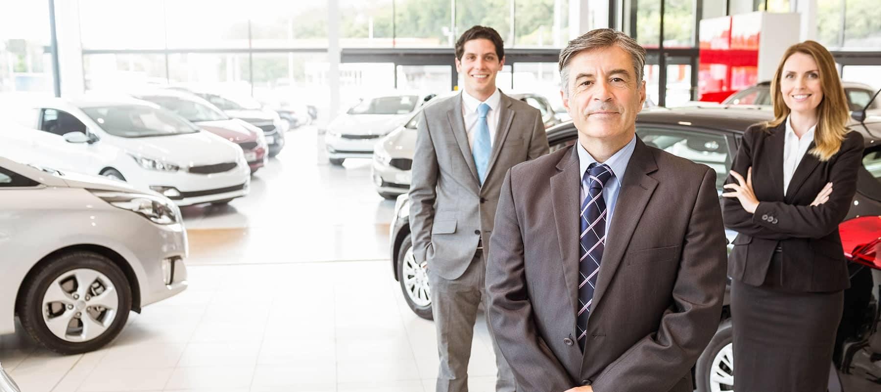 three car salesmen and saleswomen in suits standing in their showroom