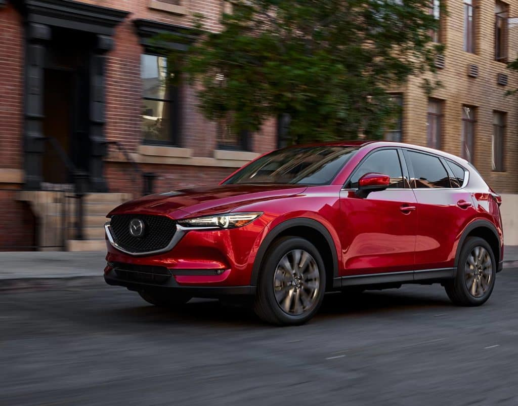 New Mazda CX-5 driving through town with bricked brownstones in background