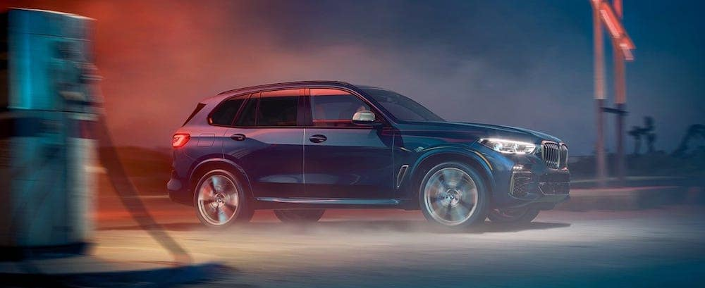 A 2020 BMW X5 driving on a dirt road at night